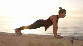 Fille caucasienne convenable mignonne dans des guêtres de sport faisant l'exercice de planche sur la plage au coucher du soleil s banque de vidéos
