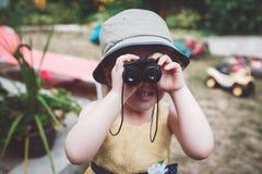Fille caucasienne mignonne dans la robe jaune et le chapeau regardant par des jumelles images stock