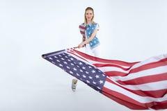 Fille caucasienne posant et ondulant le drapeau des Etats-Unis, célébration de Jour de la Déclaration d'Indépendance Photos libres de droits