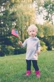 Fille caucasienne tenant et ondulant le drapeau américain en parc en dehors de célébrer le concept de jour de collecte de Jour de Photo stock