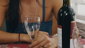 Fille causant à la table avec la bouteille de vin sur la terrasse de la maison de campagne Verre vide banque de vidéos