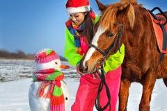 Fille, cheval et bonhomme de neige Image stock