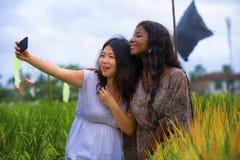 Fille chinoise asiatique d'appartenance ethnique mélangée et femme américaine d'africain noir prenant à amies le selfie avec le t images libres de droits