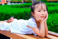 Fille chinoise se trouvant sur le banc sur son ventre Photo stock