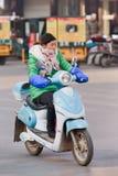 Fille chinoise sur un vélo électrique dans Hengdian, Chine Photos stock
