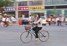 Fille chinoise sur une bicyclette avec des boutiques sur le fond, Pékin, Chine Images libres de droits