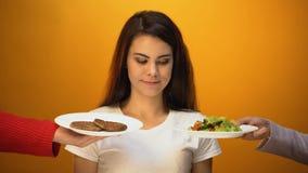 Fille choisissant la viande au lieu de la salade, rejet de veganism, nutrition saine banque de vidéos