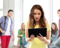 Fille choquée d'étudiant avec le PC de comprimé à l'école image stock