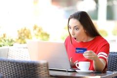 Fille choqu?e payant en ligne avec la carte de cr?dit et l'ordinateur portable photo libre de droits