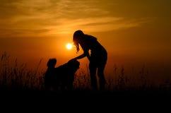Fille choyant son chien dans le coucher du soleil Photo stock