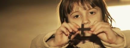 Fille chrétienne d'enfant priant le chapelet dans l'église images stock