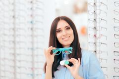 Fille comparant des contacts aux lunettes pour la correction de vision photographie stock