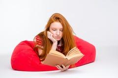 Fille concentrée détendant dans le fauteuil poire et le livre rouges de lecture Photo stock