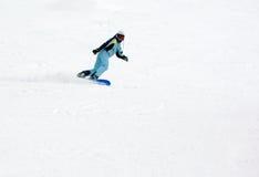 Fille conduisant rapidement sur le snowboard images stock