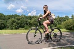 Fille conduisant une bicyclette Vue de côté Forêt et nuages à l'arrière-plan Photographie stock libre de droits