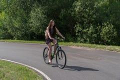 Fille conduisant une bicyclette Vue de côté Forêt et nuages à l'arrière-plan Images stock