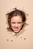 Fille contrariée piaulant par le trou en papier photo stock