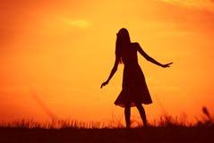 Fille contre des cieux de coucher du soleil image stock