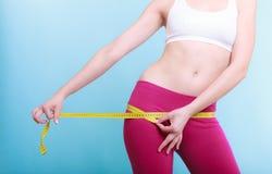 Fille convenable de femme de forme physique avec la mesure de bande de mesure ses échines Image libre de droits