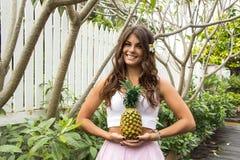 Fille convenable de sourire tenant l'ananas dans des ses mains Photo stock