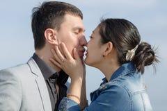 Fille coréenne embrasing et embrassant son ami européen Image libre de droits