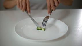 Fille coupant en tranches le concombre, hanté avec undereating, crainte du poids excessif, anorexie photographie stock