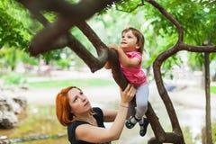 Fille courageuse s'élevant sur l'arbre Image stock