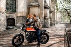 Fille courant à son ami s'asseyant sur la moto dans la vieille ville Photographie stock libre de droits