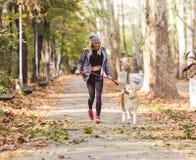 Fille courant et marchant en beau parc avec le chien d'akita Image stock
