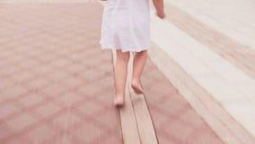 Fille courant nu-pieds sur la rue de ville dans la robe blanche banque de vidéos