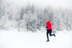Fille courant sur la neige en montagnes d'hiver Sport, inspiration de forme physique et motivation  image stock