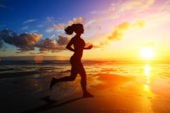 Fille courante à la silhouette de coucher du soleil Photographie stock libre de droits