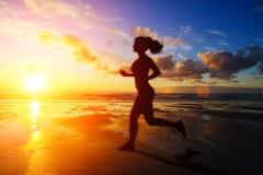 Fille courante à la silhouette de coucher du soleil Image libre de droits