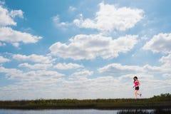 Fille courante sur un champ vert et un ciel lumineux photo stock