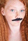 Fille couverte de taches de rousseur avec la moustache image stock