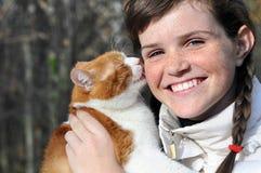 Fille couverte de taches de rousseur heureuse et chat rouge drôle Photo stock