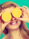 Fille couvrant ses yeux d'agrumes de citron image libre de droits