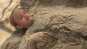 Fille creusant dans le sable sur la plage Avoir l'amusement et le concept de joie Petite belle fille jouant avec le sable de mer  banque de vidéos