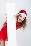 Fille criarde dans la robe rouge dans un chapeau de Noël tenant des bannières Image stock
