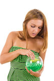 Fille curieuse avec le bol en verre et la fleur à l'intérieur Images stock