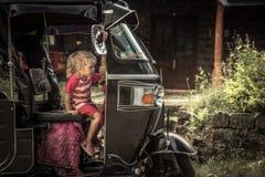 Fille curieuse de voyageur d'enfant sur le véhicule à moteur de tuk de tuk pendant le mode de vie insouciant heureux de déplaceme photos stock