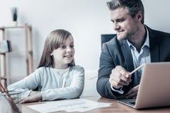 Fille curieuse interrogeant le père au sujet de son travail photo stock