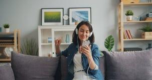 Fille décontractée heureuse écoutant la musique dans des écouteurs tenant le smartphone banque de vidéos