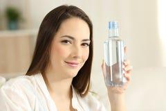 Fille décontractée montrant une bouteille d'eau générique images libres de droits