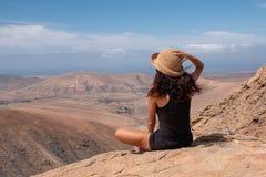 Fille décontractée regardant un paysage du haut d'une montagne photographie stock libre de droits