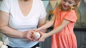 Fille décorant des biscuits de Pâques avec la grand-mère banque de vidéos
