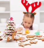 Fille décorant des biscuits de pain d'épice Photographie stock