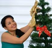 Fille décorant un arbre de Noël Photos stock