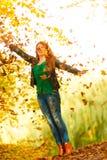 Fille détendant dans des feuilles de lancement de parc d'automne dans le ciel Photo stock