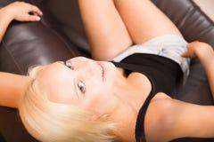 Fille détendant sur un sofa Image stock